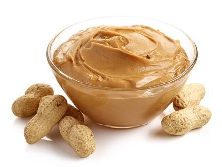 46966846-glass-bowl-of-peanut-butter-with-peanuts-isolated-on-white-background